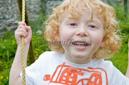boy smiling on swing