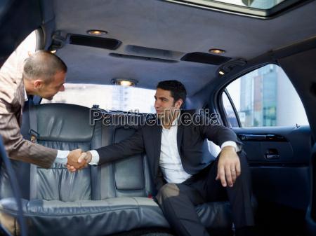 businessmen shaking hands in limousine