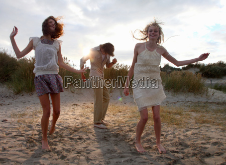 friends dancing at the beach at