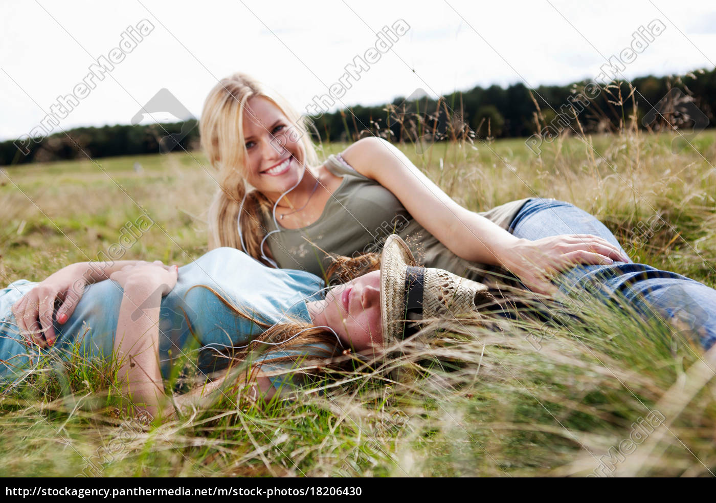 two, young, women, laying, in, grass - 18206430