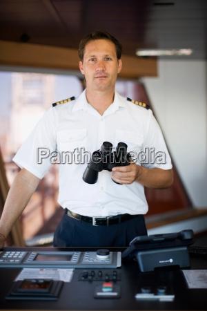 captain, holding, binoculars, in, his, hands - 18207068