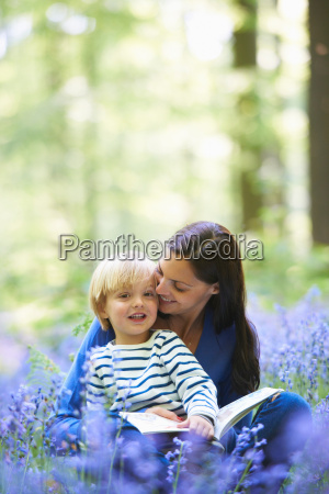 mother and son reading in forest