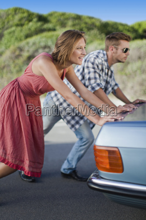 couple pushing broken down car