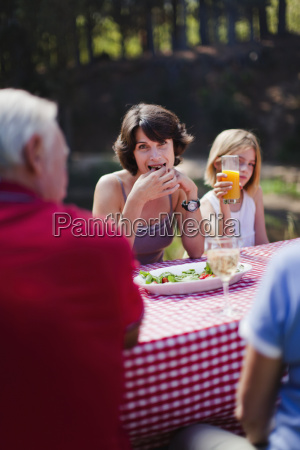 woman eating with family at picnic