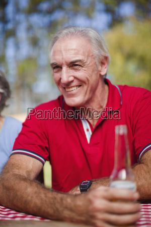 older man drinking at picnic table