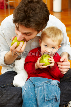 father and son eating apples together