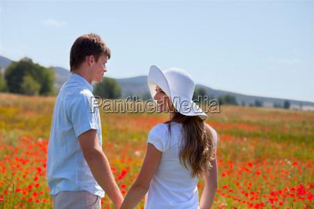 couple walking in field of poppies