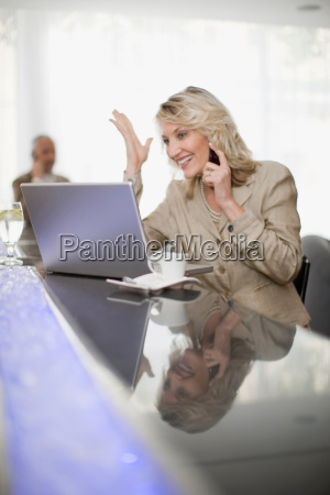 businesswoman on phone using laptop