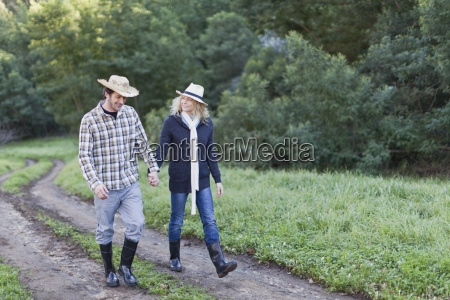 smiling couple walking on dirt path