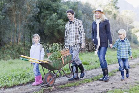 family with wheelbarrow on dirt path