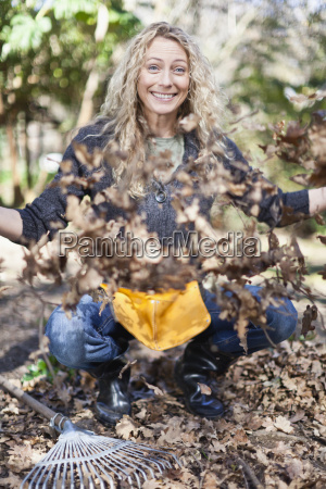 smiling woman playing with dead leaves
