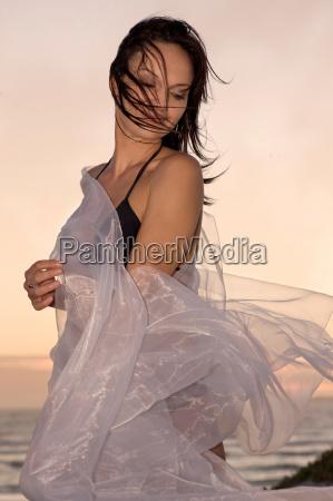 woman playing with sarong on beach