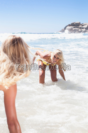 women playing in waves on beach
