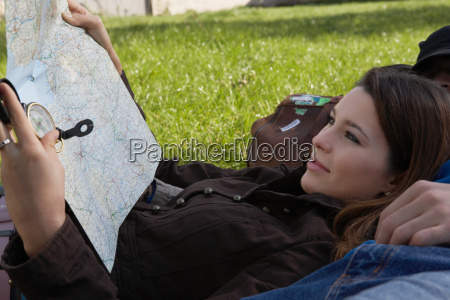 woman smiling holding map reclining