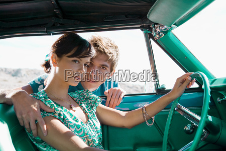 man leaning into car holding woman