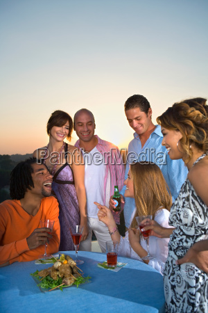 young people having dinner at sunset