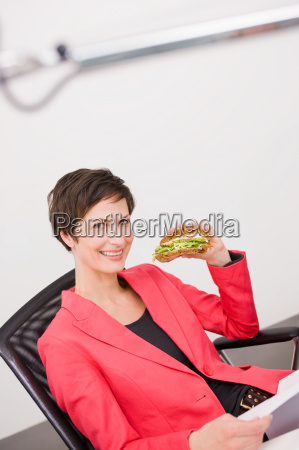 woman eating sandwich at her office