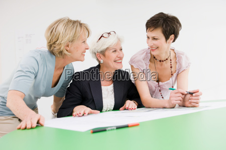 three women studying some papers