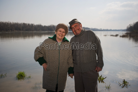 senior couple by river holding hands