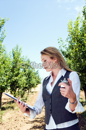 woman with stopwatch in orchard