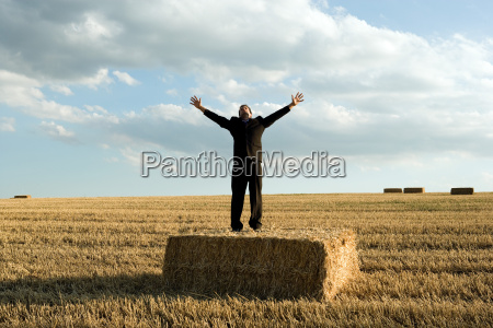 man standing on hay in wheat