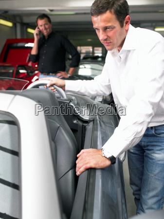 two men in a garage looking