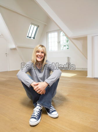 smiling seated woman on wooden floor