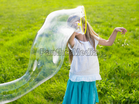 little girl making soap bubbles
