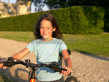 young girl on bicycle looking at