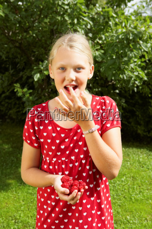 young girl eating fresh raspberries