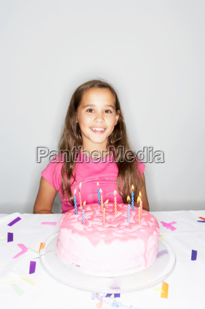 girl with birthday cake candles lit