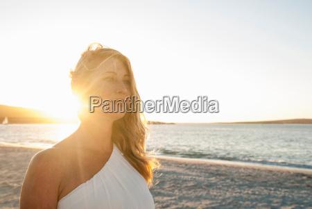 blond woman on beach at dusk