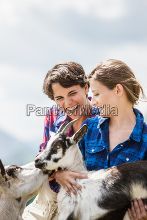 two female friends with goats