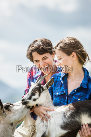 young women holding kid goats tyrol