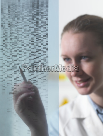 female researcher examining dna autoradiogram gel