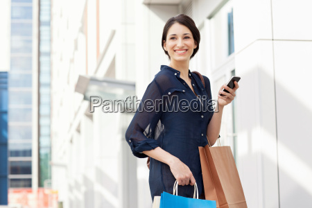 young businesswoman carrying smartphone and shopping