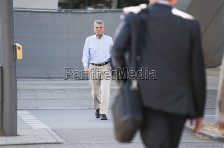 senior adult businessman walking down street