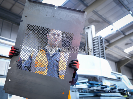 worker inspecting parts next to robotic