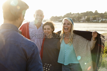 four adult friends with picnic blanket