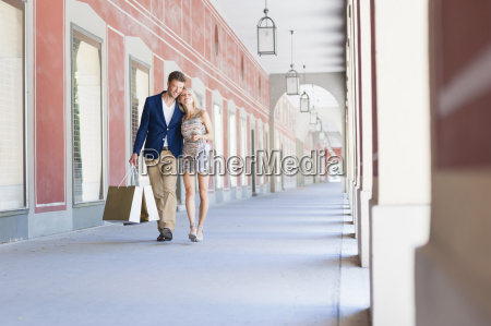 smiling couple carrying shopping bags in