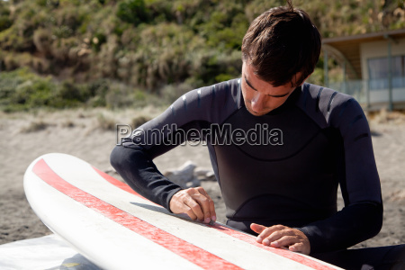 young adult male surfer waxing board