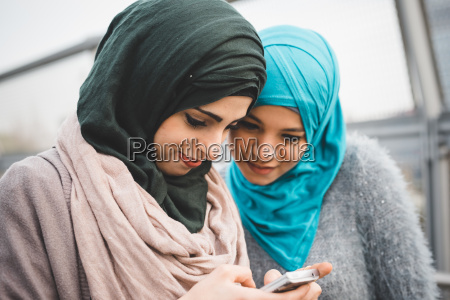 two young female friends reading smartphone