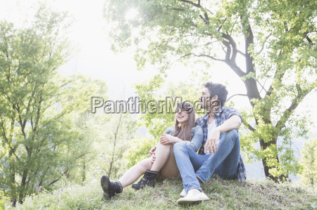 young couple sitting on grass piemonte