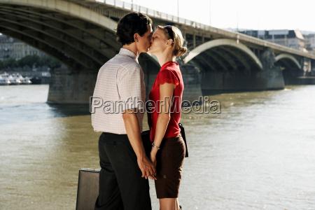 couple kissing by a bridge