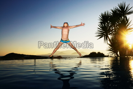 young boy jumping into an infinity