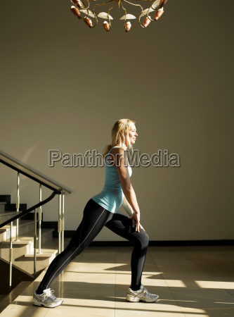 woman stretching by steps side view