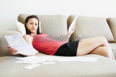 reclined woman looking at paperwork