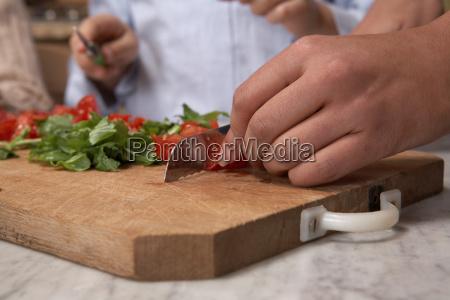 woman chopping tomatos on board