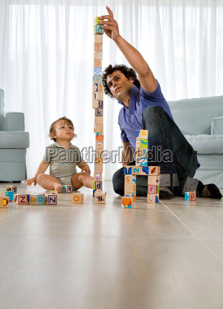 baby watching father building cube tower
