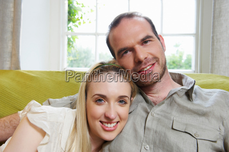 couple sitting on couch smiling